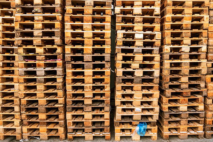 A lot stacks of used  wooden pallets of euro type on warehouse is ready for recycling. Industrial background. Close-up. Outdoors.